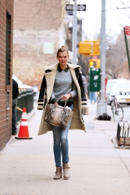 Supermodel Karlie Koss, wearing a black lambswool coat, jeans, gray suede ankle boots with buckles, and carrying a snakeskin Michael Kors bag, walks in West Village in New York City